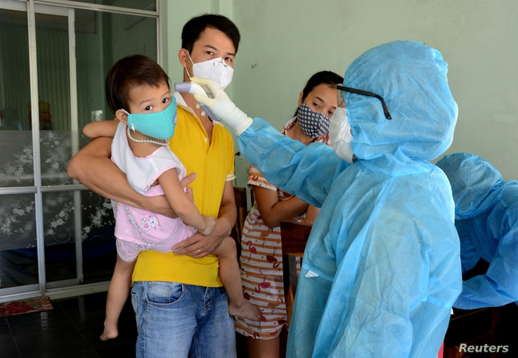 A health worker checks the temperature of residents at the area of a newly found coronavirus infected patient in Da Nang city, Vietnam, July 26, 2020.
