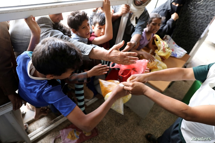 People crowd to get food rations from a charity kitchen in Sana'a, Yemen, July 20, 2020.