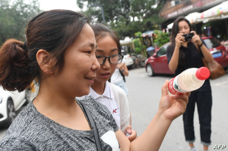 This photo taken on July 12, 2018 shows a woman looking at polluted water in a mineral water bottle at a roving exhibition…