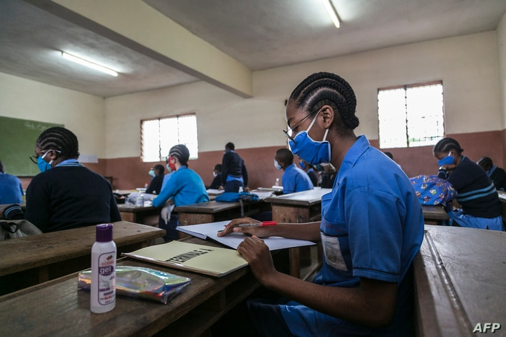 Students wear face masks as a preventive measure against the spread of the COVID-19 coronavirus in their classroom at the  Jean…