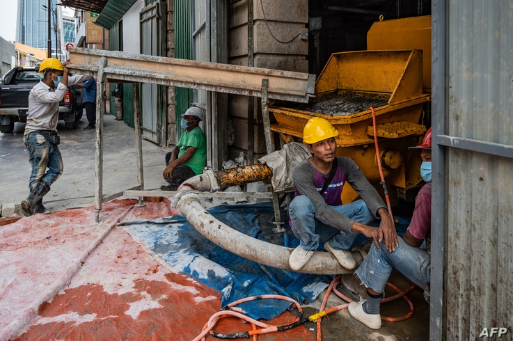 Workers rest at a construction site in Kuala Lumpur on July 3, 2020. (Photo by Mohd RASFAN / AFP)