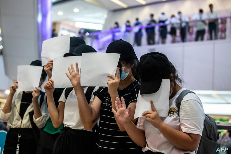 Protesters hold up blank papers during a demonstration in a mall in Hong Kong on July 6, 2020, in response to a new national…