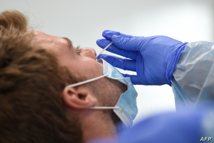 A healthcare worker uses a swab to collect a sample from a man testing for the novel coronavirus COVID-19 at a primary health…