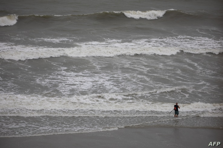 Dark clouds and high surf produced by Tropical Storm Isaias can be seen as a man continues to fish on the beach in North Myrtle…
