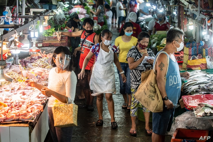 People wearing masks shop for fresh food at a market in Manila on August 6, 2020. - The Philippines plunged into recession…