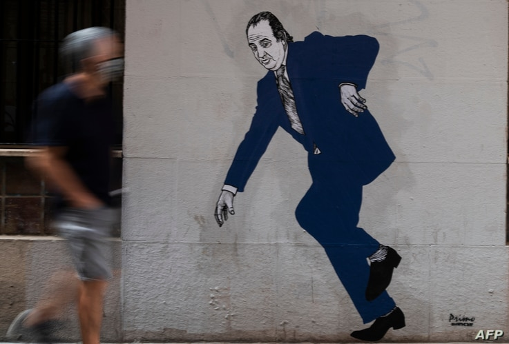 A man wearing a face mask walks past a graffiti by artist El Primo de Bansky (the cousin of Bansky) of former Spanish King Juan…