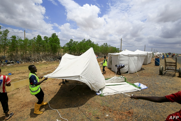 Sudanese men help erect a tent on the side of the road for displaced families, as a result of flooding and torrential rain, in the town of Osaylat, 50 km southeast of the capital Khartoum, on Aug. 6, 2020.