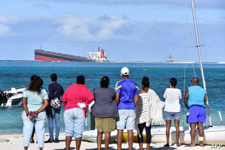 Bystanders look at MV Wakashio bulk carrier that had run aground and from which oil is leaking near Blue Bay Marine Park in…