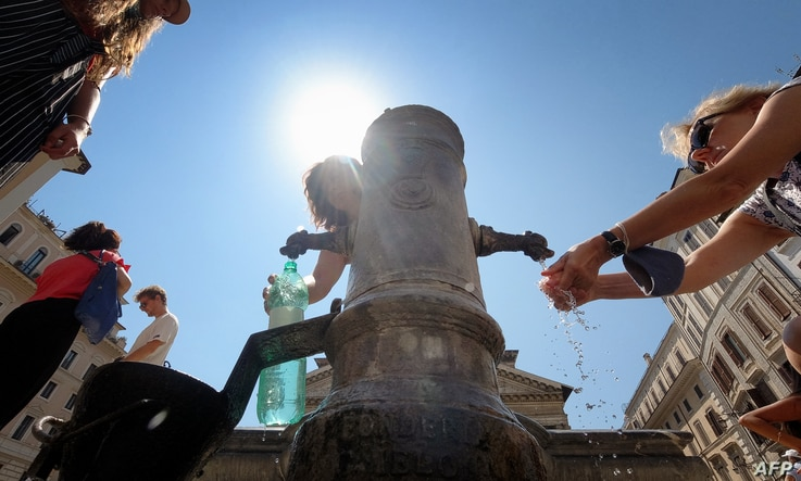 "A tourist refreshes himself and fills bottle of water in a ""Nasone"" fountain in the center of Rome on August 12, 2020. -…"