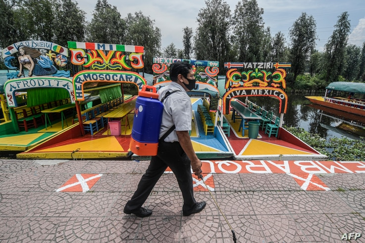 A man disinfects the Cuemanco canal pier in Xochimilco, a network of canals and floating gardens that is one of Mexico City's…