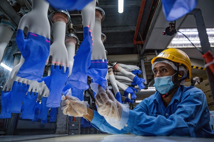 A worker inspects disposable gloves at the Top Glove factory in Shah Alam on the outskirts of Kuala Lumpur on August 26, 2020. …