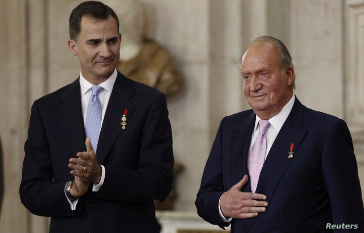 Spain's King Juan Carlos (R) reacts next to his son Crown Prince Felipe during the signature ceremony of the act of abdication…