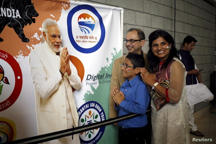 A group of attendees gesture in front of a poster of Indian Prime Minister Narendra Modi before a community reception at SAP…