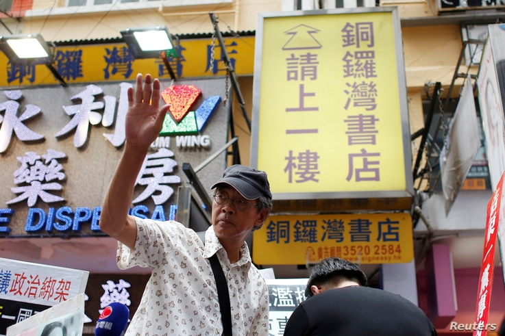 Bookseller Lam Wing-kee waves to supporters outside his Causeway Bay Books bookstore before taking part in a protest march in…