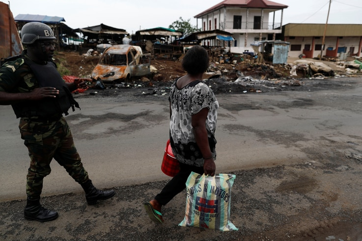 A woman walks past a Cameroonian elite Rapid Intervention Battalion (BIR) member in the city of  Buea in the anglophone southwest region, Cameroon, Oct. 4, 2018.