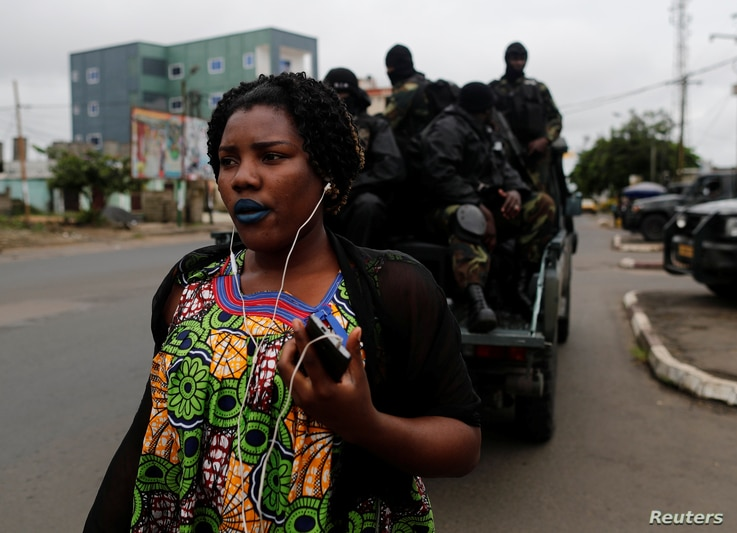 FILE - A woman  walks past  Cameroonian elite Rapid Intervention Battalion (BIR) members as they sit on their military vehicle during their patrol in the city of  Buea in the anglophone southwest region, Cameroon, Oct. 4, 2018.