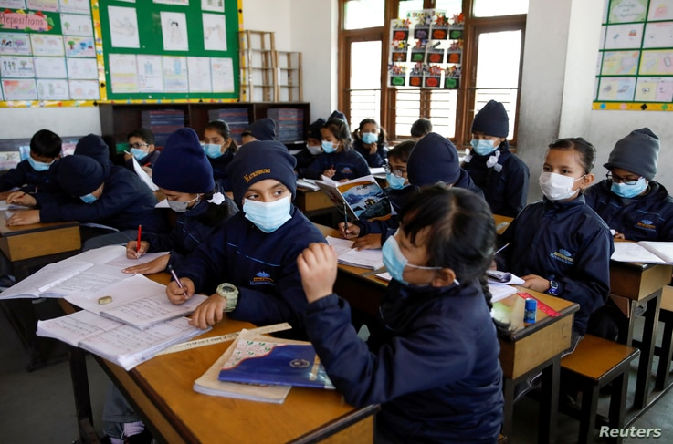 Children wearing facial masks, as a precaution after Nepal confirmed the first case of coronavirus in the country, attend a…
