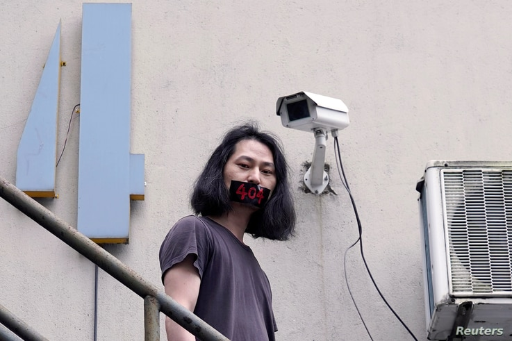 Brother Nut, Chinese performance artist with taped mouth poses for a picture in Shanghai, following the coronavirus disease …