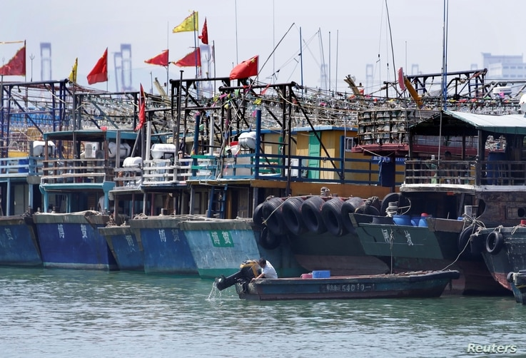 FILE PHOTO: A fisherman lifts the propeller up next to anchored boats at a fishing harbour, as Typhoon Mangkhut approaches, in…