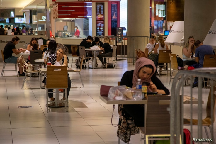 People eat in the foodcourt at the Eaton Centre shopping centre after indoor dining restaurants, gyms and cinemas re-open under…