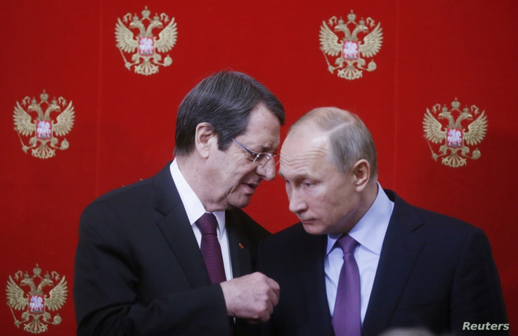 FILE PHOTO: Russian President Vladimir Putin (R) and Cypriot President Nicos Anastasiades attend a signing ceremony following…