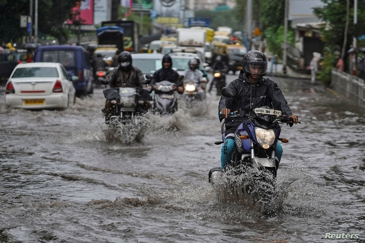 People drive through a flooded street during heavy rains in Mumbai, India, August 4, 2020. REUTERS/Hemanshi Kamani