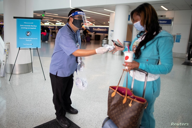 Travel Safely Ambassador Carlos Hernandez hands out a face masks to an airline passenger at LAX airport.