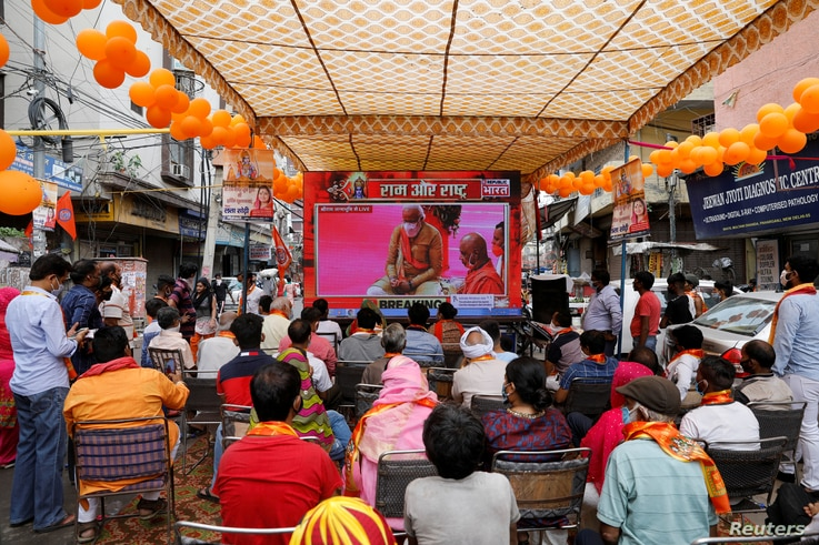 People watch a live screening of the stone laying ceremony of the Ram Temple by Prime Minister Narendra Modi in Ayodhya, in New…