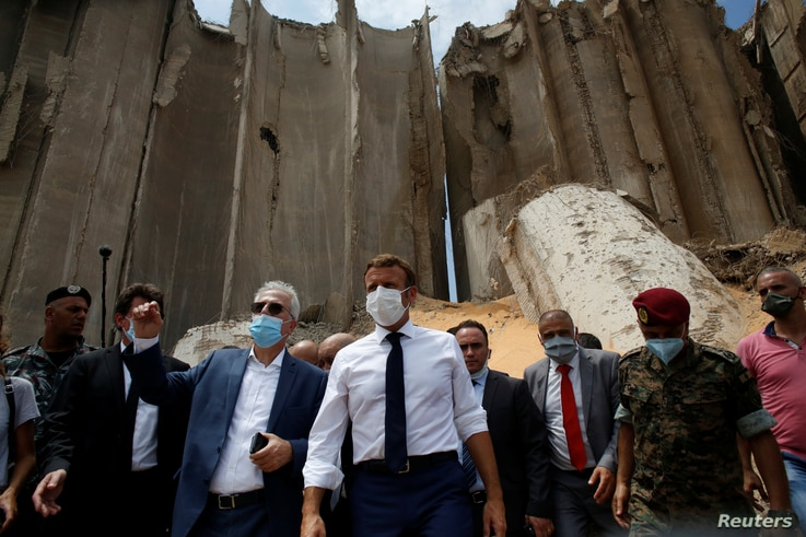 French President Emmanuel Macron  gestures as he visits the devastated site of the explosion at the port of Beirut, Lebanon.