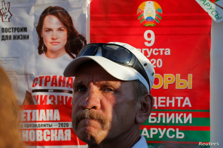 A man stands next to an election campaign poster during a rally held by supporters of Svetlana Tikhanouskaya, a candidate in…