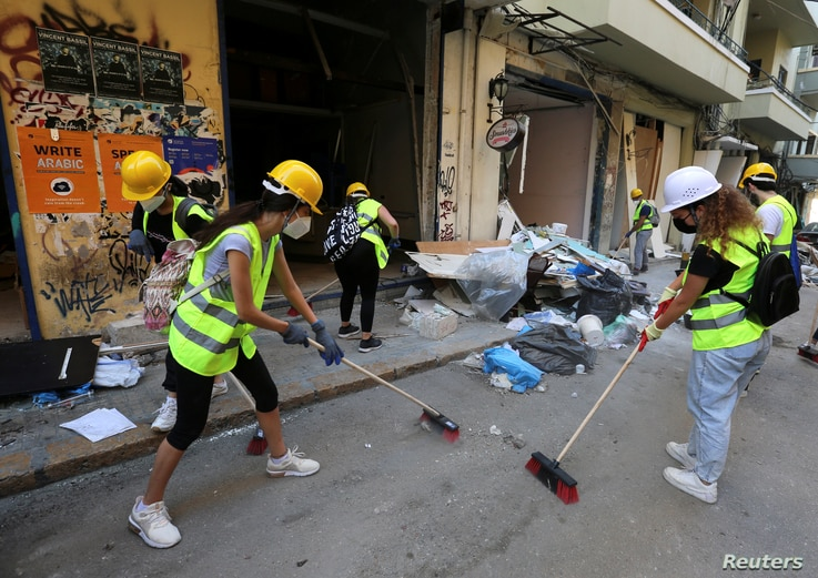 Volunteers clean debris from the street following Tuesday's blast in Beirut's port area, Lebanon, Aug. 7, 2020.