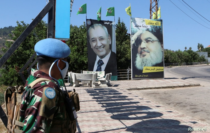 A United Nations peacekeeper (UNIFIL) stands near a poster depicting Lebanon's Hezbollah leader Sayyed Hassan Nasrallah, in…