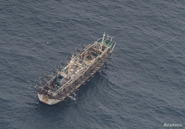A fishing boat is seen from an aircraft of the Ecuadorian navy after a fishing fleet of mostly Chinese-flagged ships was…