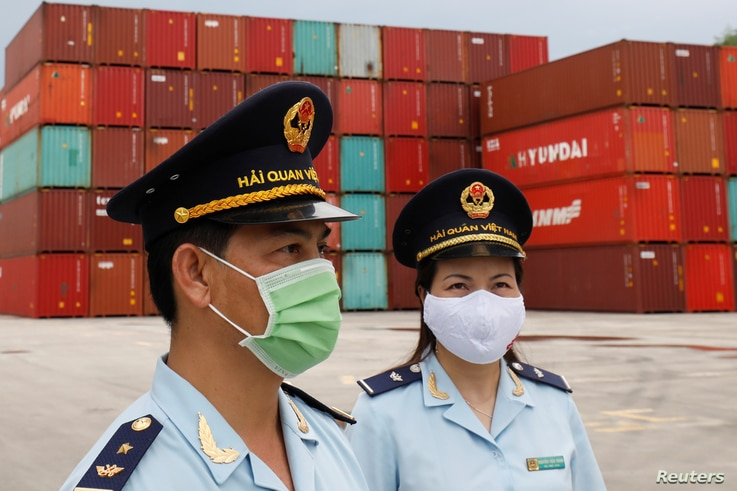 Vietnamese customs officers wearing protective masks patrol at a containers port, amid the spread of the coronavirus disease …