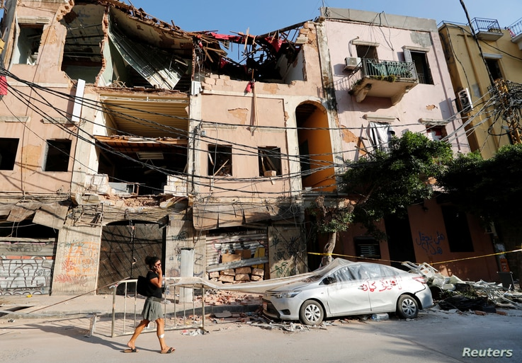 A woman walks past a damaged area in the aftermath of a massive explosion in Beirut, Lebanon August 13, 2020. REUTERS/Thaier Al…