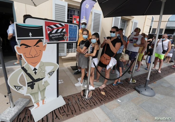 Tourists wearing protective face masks line up to visit the Gendarmerie and Cinema Museum in Saint Tropez as France reinforces…