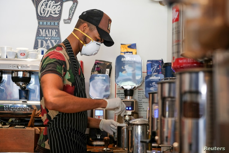 A worker wears a protective face mask as he prepares coffee at a cafe following the outbreak of the coronavirus disease (COVID…