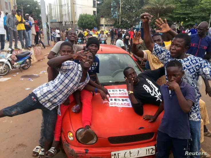 Opposition supporters react to the news of a possible mutiny of soldiers in the military base in Kati, outside the capital.