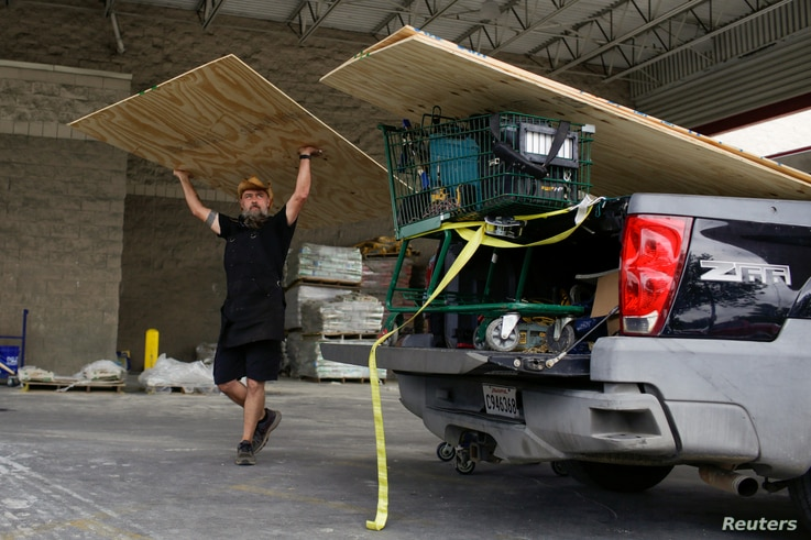 Paul Humphrey, of New Orleans, loads plywood into his truck, to board a friend's home in preparation for the arrival of hurricanes Marco and Laura, which are forecasted to move onshore Monday and Thursday, at Lowe's in New Orleans, Louisiana, U.S., Aug. 23, 2020.