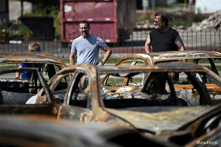 People stand in front of the damage at Car Source, a used car lot on Sheridan Road, after protests following the police…