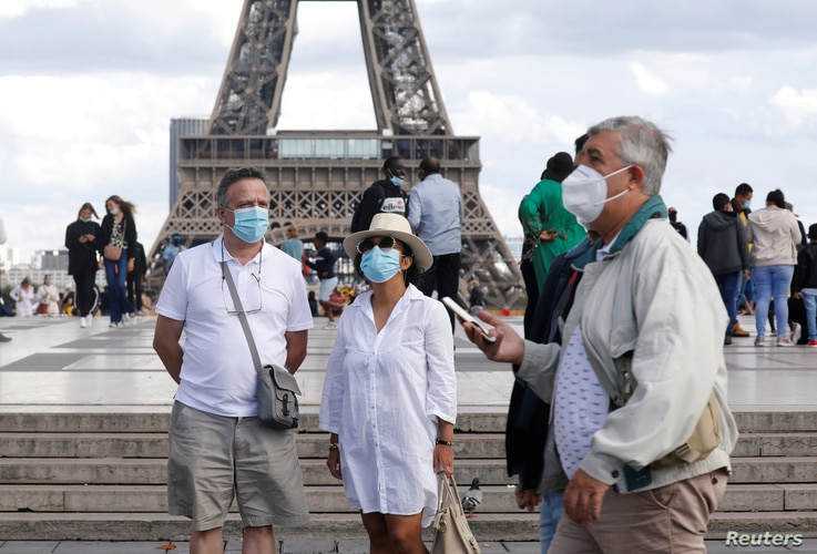 People wearing protective masks stand at the Trocadero square near the Eiffel Tower as France reinforces mask-wearing as part…