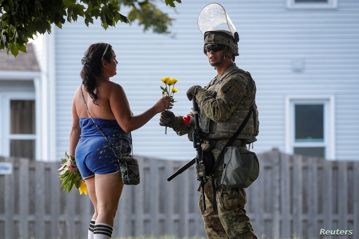 A woman hands flowers to a member of the Wisconsin National Guard standing by as people gather for a vigil, following the…