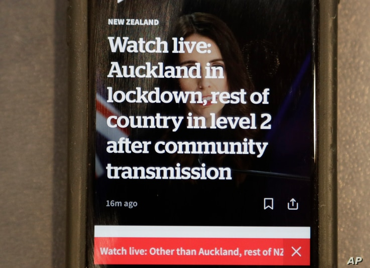 A news alert is displayed on a mobile phone in Christchurch, New Zealand, Tuesday, Aug. 11, 2020. New Zealand Prime Minister…