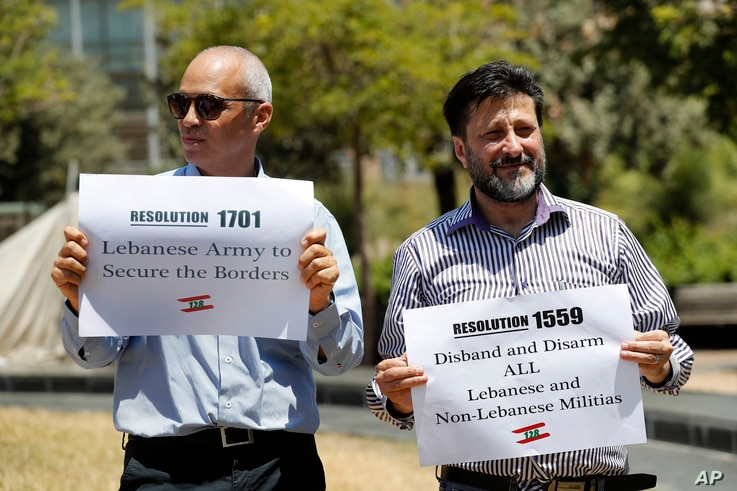 FILE - In this July 24, 2020 file photo, anti-Hezbollah protesters hold banners with the U.N. Resolution 1559, which called for…
