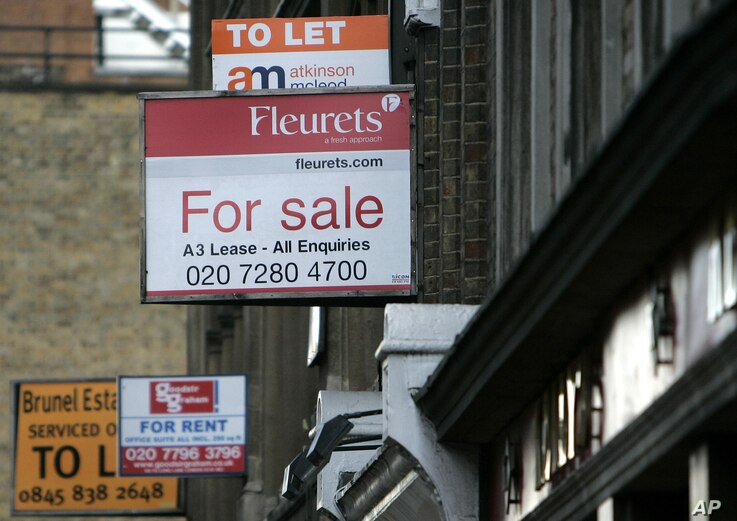 FILE - Property advertisements are seen in central London.