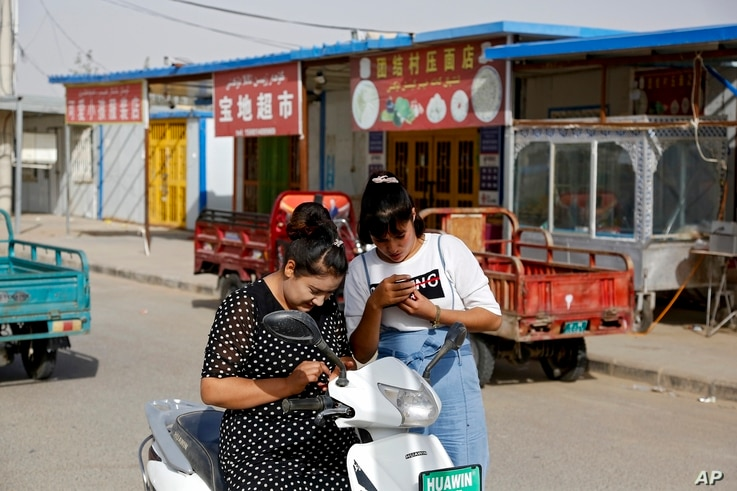 In this Sept. 20, 2018 photo, Uighur women look at their smartphones near restaurants and shophouses operated by Uighurs at the…