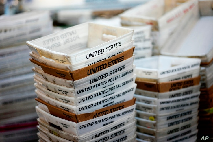 FILE- In this Dec. 14, 2017, file photo, boxes for sorted mail are stacked at the main post office in Omaha, Neb. A task force…
