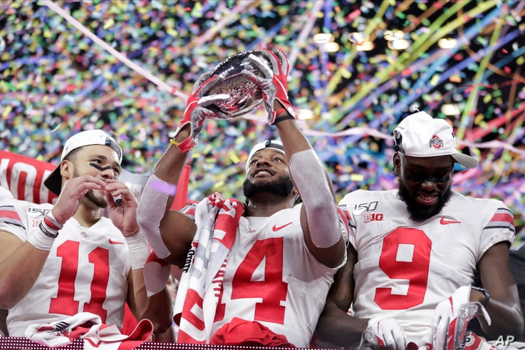 Ohio State wide receiver K.J. Hill (14) holds the trophy following the team's 34=21 win over Wisconsin in the Big Ten…