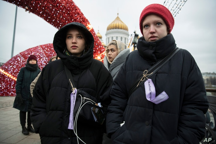 Women stay in a line to hold a banner during an action against domestic violence on the Patriarshy Bridge, with the Cathedral…