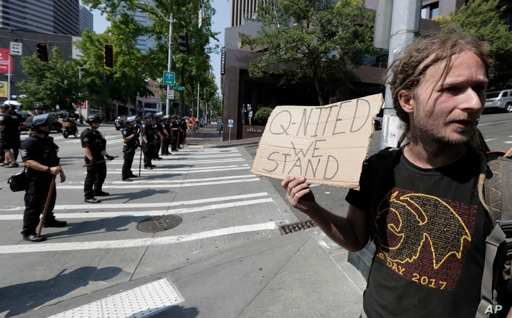 "In this Aug. 18, 2018 file photo man holds a sign that reads ""Q-Nited We Stand"" during a rally in Seattle."
